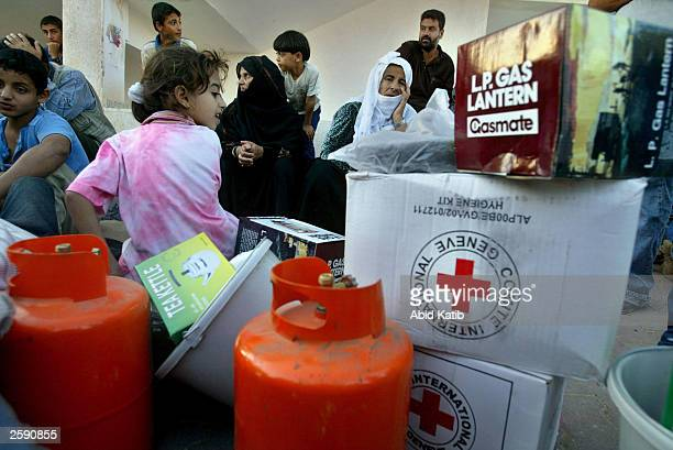 Homeless Palestinians receive aid from an international committee of the Red Cross and Red Crescent at an aid distribution center at a local sports...