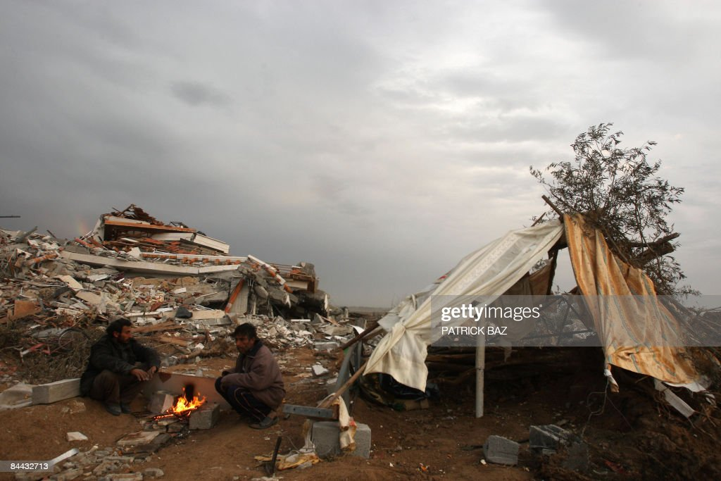 Homeless Palestinians sit around a bonfire next to a makeshift tent amid the ruins of the Israelibombed Jabalia neighbourhood of Ezbet Abed Rabbo on...