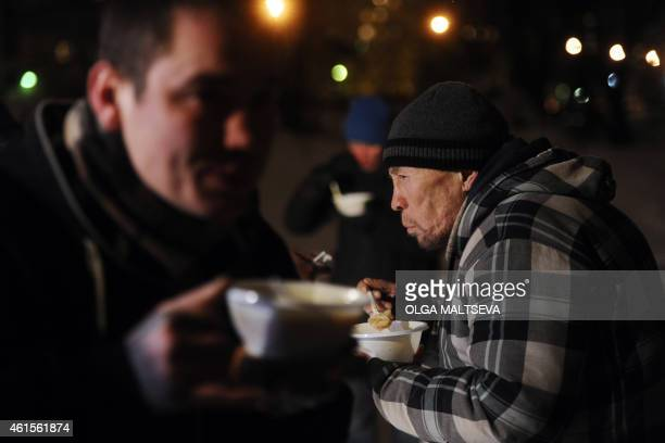 Homeless people eat hot food near a shelter tent provided by a charity organisation in the Russia's second city of St Petersburg on January 13 2015...
