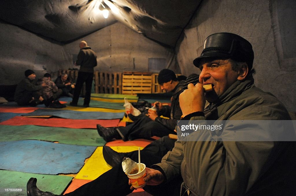 Homeless people eat in a shelter tent provided by a charity organisation in the Russia's second city of Saint-Petersburg on December 3, 2012. AFP PHOTO / OLGA MALTSEVA