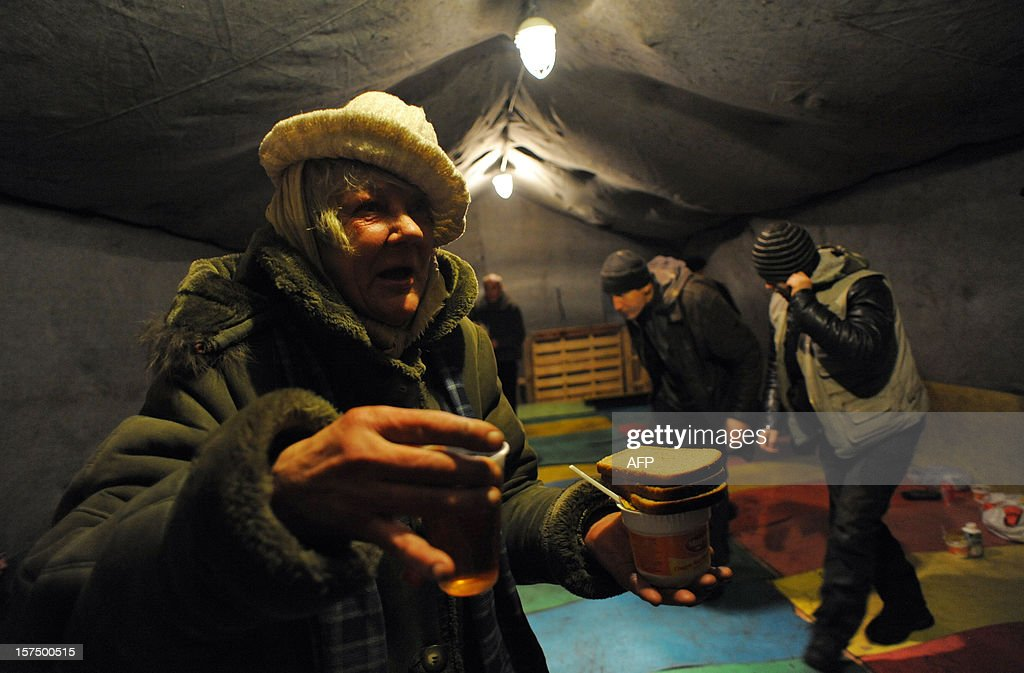 Homeless people receive food in a shelter tent provided by a charity organisation in the Russia's second city of Saint-Petersburg on December 3, 2012.