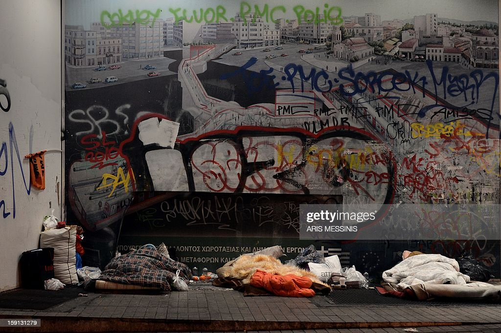 Homeless people sleep outside a metro station in central Athens on January 8, 2013. With low temperatures hitting Greece's capital, municipal officials have opened few temporary shelters for people sleeping rough during the cold snap.