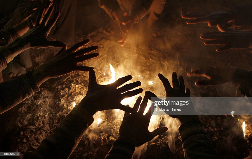 Homeless people warm their hands to beat cold in the coldest evening on January 3, 2013 in New Delhi, India. A cold wave is sweeping across north India sending temperatures plunging. Delhi Wednesday witnessed the coldest day in the past 44 years.