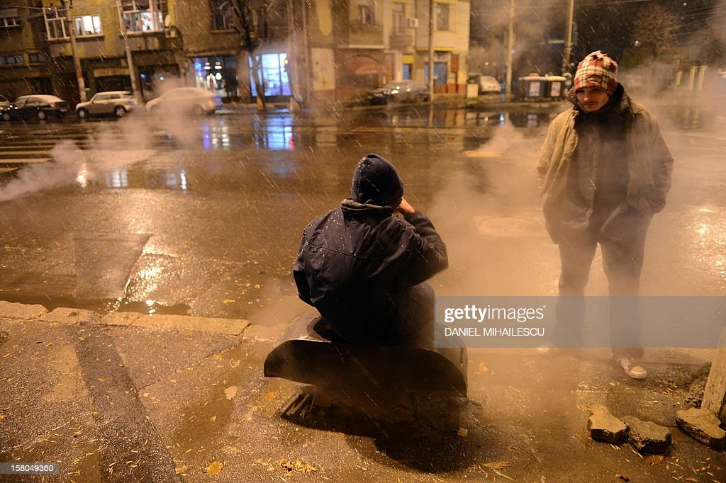 Homeless people warm-up at an air pit of a heating system in Bucharest, on December 9, 2012. Romania's centre-left governing coalition has comfortably won a weekend parliamentary poll with nearly 60 percent of the vote, partial results showed on December 10, 2012. AFP PHOTO / DANIEL MIHAILESCU