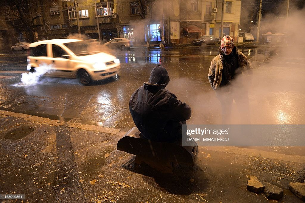Homeless people warm-up at an air pit of a heating system in Bucharest, on December 9, 2012. Romania's centre-left governing coalition has comfortably won a weekend parliamentary poll with nearly 60 percent of the vote, partial results showed on December 10, 2012.