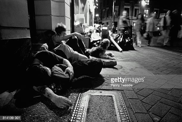 Homeless people with dogs huddled together on pavement, night (b&w)