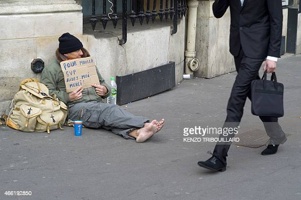 A homeless person begs on March 14 2015 in Paris AFP PHOTO / KENZO TRIBOUILLARD