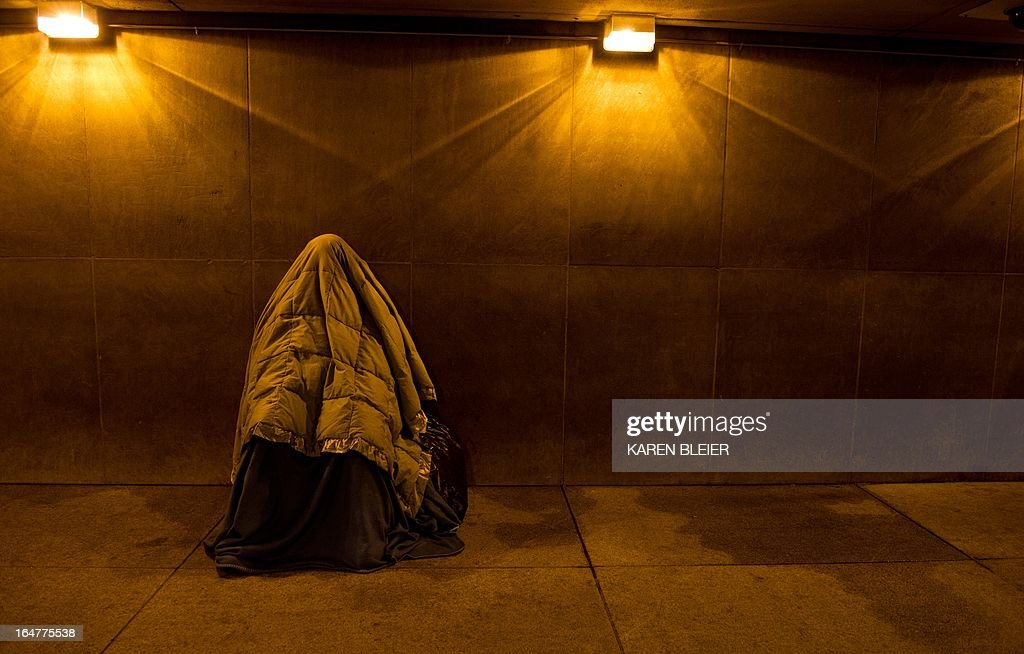 A homeless person covered in blankets for warmth, sleeps at the entrance of a Metro station near the White House, March 28, 2013 in Washington, DC. AFP PHOTO / Karen BLEIER