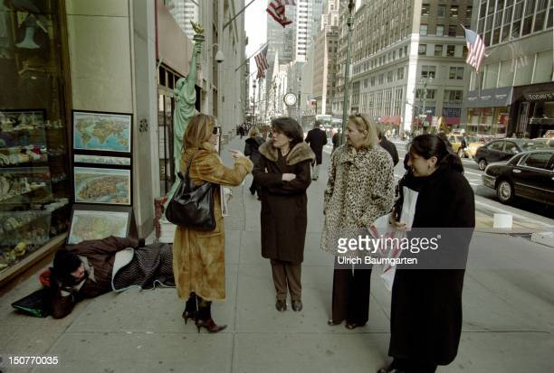 Homeless person in the 5th AV model of the statue of liberty and wealthy women