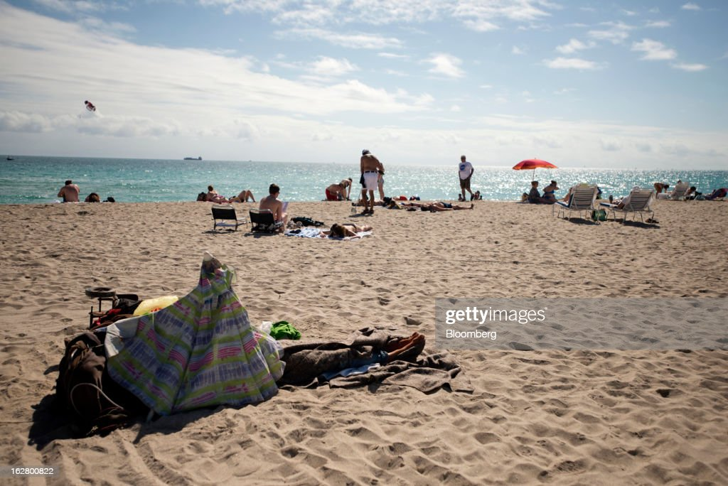 A homeless person lies in the sand in the South Beach neighborhood of Miami Beach, Florida, U.S., on Wednesday, Feb. 20, 2013. U.S. exports in the travel and tourism sector reached $168.1 billion in 2012, up 10.1 percent from the year-ago level of $152.7 billion, according to data released Feb. 22 by the Commerce Department's International Trade Administration. Photographer: Ty Wright/Bloomberg via Getty Images