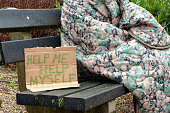 Homeless person wrapped in camouflage blanket sitting on park bench with handwritten cardboard sign asking for help