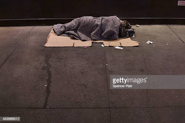 A homeless person sleeps on a Manhattan street on August 22 2014 in New York City According to the Department of Homeless Services the number of...