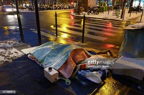 A homeless person sleeps on a sidewalk in Paris on December 2 2010 as snow and freezing temperatures severely hit Europe Heavy snowfalls forced some...