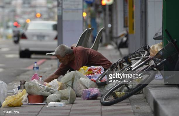 A homeless person sorts out his belongings on a side walk in New Taipei City after Typhoon Nesat slashed Taiwan on July 30 2017 Taiwan suffered...
