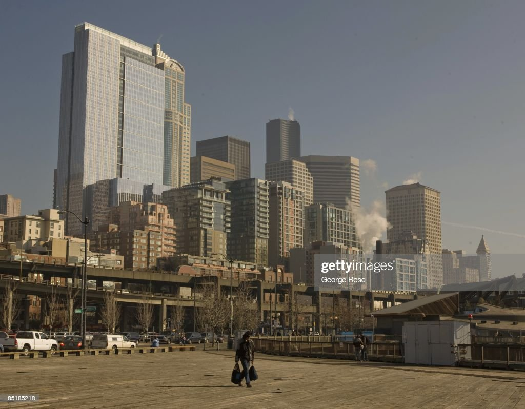 A homeless person walks along the waterfront with high rise offices and condominium buildings in the background in this 2009 Seattle Washington city...