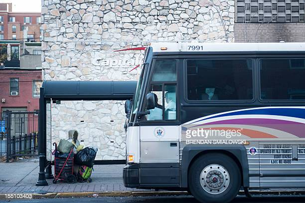 A homeless person watches as a New Jersey Transit bus arrives at a bus stop on November 1 2012 in Hoboken New Jersey Hurricane victims continue to...
