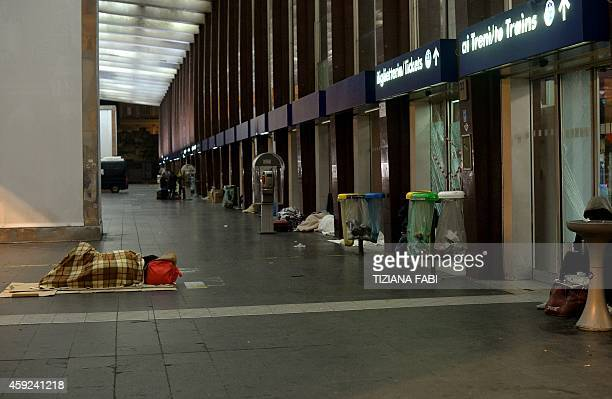 Homeless persons sleep in front of shop windows at the Termini train station on November 18 2014 in Rome AFP PHOTO / TIZIANA FABI