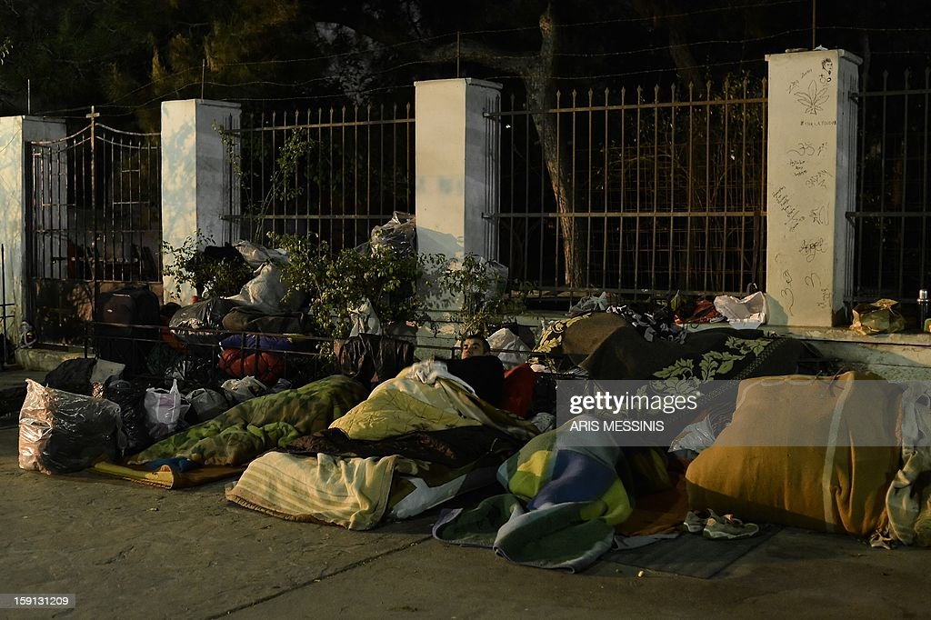 A homeless prepares to sleep under a road bridge in Athens on January 8, 2013. With low temperatures hitting Greece's capital, municipal officials have opened few temporary shelters for people sleeping rough during the cold snap. AFP PHOTO / ARIS MESSINIS