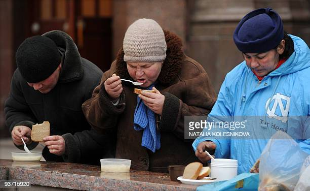 Homeless Russians eat a hand out meal distributed by a local initiative group in Moscow on December 3 2009 The Russian economy will shrink by 8587...
