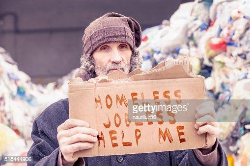 homeless show a help message written on a cardboard : Stock Photo