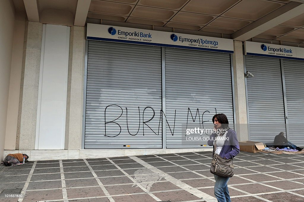 Homeless sleep by a bank in the center of Athens, featuring a graffito, reading 'Burn Me,' on June 5, 2010 during a demonstration called by two main unions against the government's austerity measures. Thousands of demonstrators gathered on June 5 in Greece to protest against a controversial, debt-dictated pension reform proposal that includes cuts, higher contributions and tougher retirement rules. AFP PHOTO/ Louisa Gouliamaki