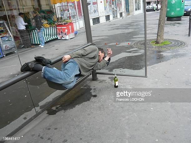 Homeless sleeping on a bench of bus shelters a bottle of red wine near him in a Parisian street on March 16 2008 in Paris France