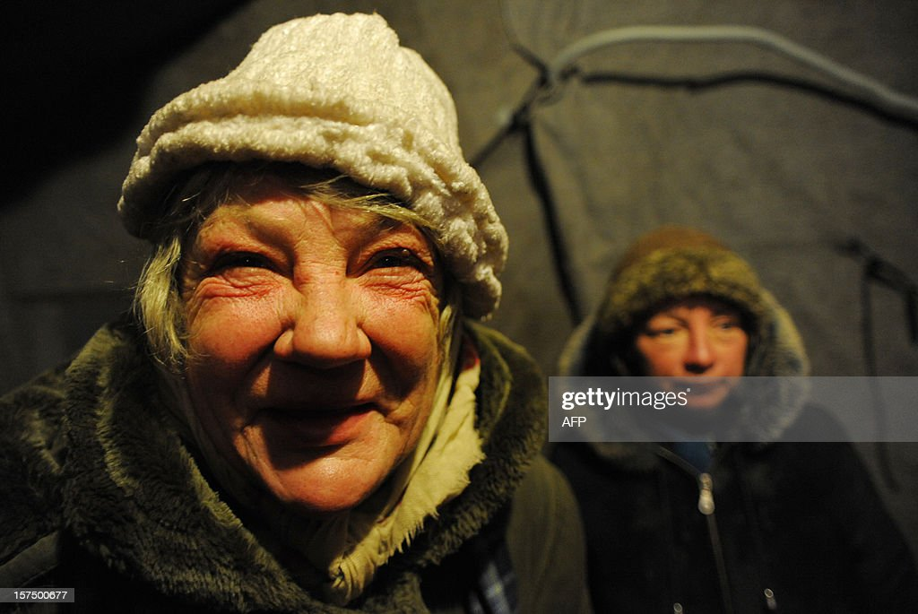 A homeless smiles in a shelter tent provided by a charity organisation in the Russia's second city of Saint-Petersburg on December 3, 2012. AFP PHOTO / OLGA MALTSEVA