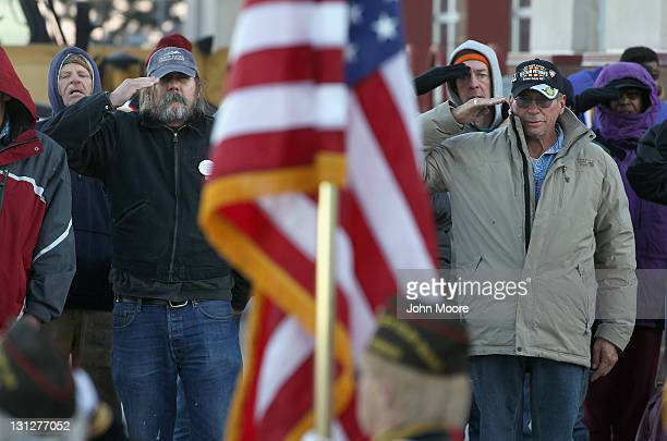 Homeless US military veterans salute the flag during the Pledge of Allegiance at a 'Stand Down' event hosted by the Department of Veterans Affairs on...
