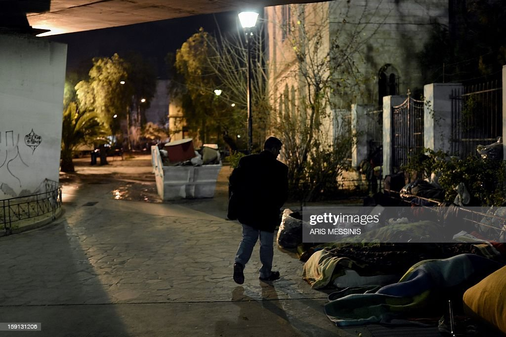 A homeless walks next to other homeless people sleeping under a road bridge in Athens on January 8, 2013. With low temperatures hitting Greece's capital, municipal officials have opened few temporary shelters for people sleeping rough during the cold snap.