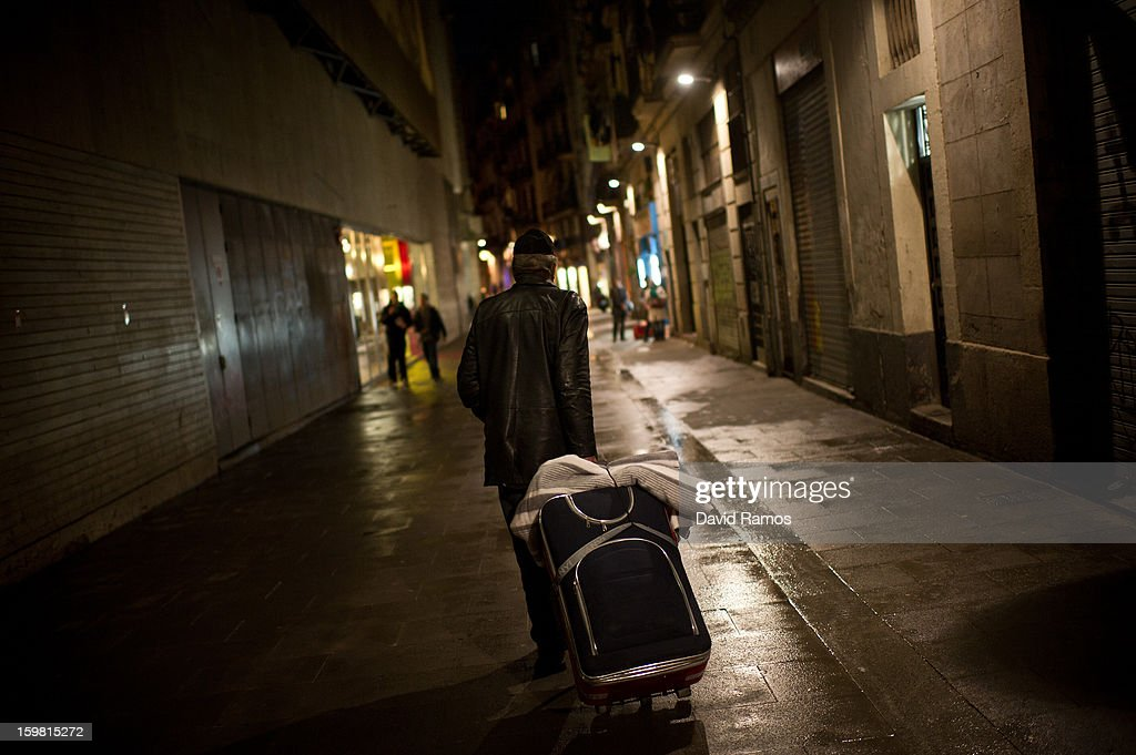 A homeless walks the street after dining at the 'El Chiringuito de Dios' ('the Stall of God') on January 11, 2013 in Barcelona, Spain. The German pastor Wolfgang Striebinger has lived in Barcelona since 1991, originally employed to minister to youths during the Barcelona Olympic Games, he decided to stay and since 2000 has run 'El Chinguito de Dios' (The Stall of God). In his mission to support the homeless, Wolfgang and his volunteers offer a place for up to 200 people to come and have some food daily and also offering them assistance with grooming and clothes. Many of the volunteers are homeless and help out in return for meals and a bed. Wolfgang's ethos is to provide peace, calm and dignity to all those that need it amongst Barcelona's burgeoning homeless population. Due to the economic situation his doors are now also open to the long term unemployed and families with little or no income. According to the latest figures 21.8% of the Spanish populations are living below the poverty line.