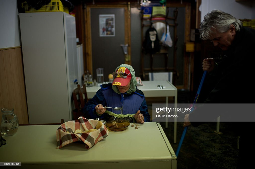A homeless wearing a baseball cap of Spain dines at the 'El Chiringuito de Dios' ('The Stall of God') on January 4, 2013 in Barcelona, Spain. The German pastor Wolfgang Striebinger has lived in Barcelona since 1991, originally employed to minister to youths during the Barcelona Olympic Games, he decided to stay and since 2000 has run 'El Chinguito de Dios' (The Stall of God). In his mission to support the homeless, Wolfgang and his volunteers offer a place for up to 200 people to come and have some food daily and also offering them assistance with grooming and clothes. Many of the volunteers are homeless and help out in return for meals and a bed. Wolfgang's ethos is to provide peace, calm and dignity to all those that need it amongst Barcelona's burgeoning homeless population. Due to the economic situation his doors are now also open to the long term unemployed and families with little or no income. According to the latest figures 21.8% of the Spanish populations are living below the poverty line.