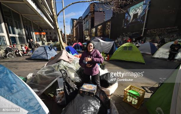 A homeless woman gets out of her tent for breakfast set up in Martin Place which has become known as 'Tent City' as homeless people set up camp in...