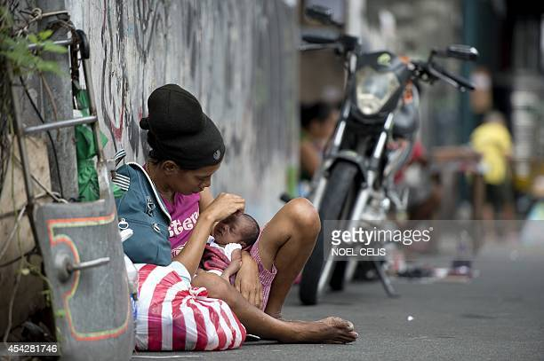 Homeless woman Inday Ibayo holds her onemonthold baby along a street in Manila on August 28 2014 The Philippine economy rebounded to post 64percent...