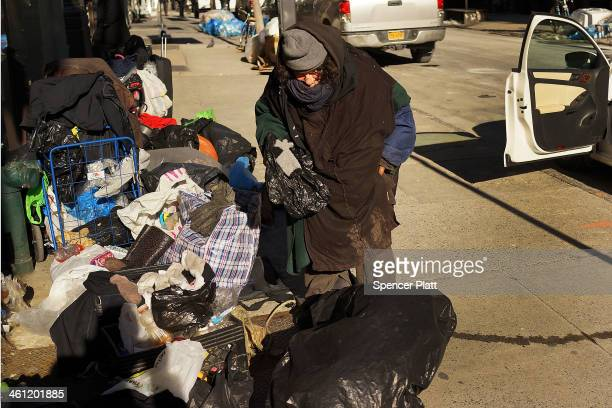 A homeless woman is layered in clothes as she sorts her possesions during subzero cold weather on January 7 2014 in New York City A 'polar vortex'...