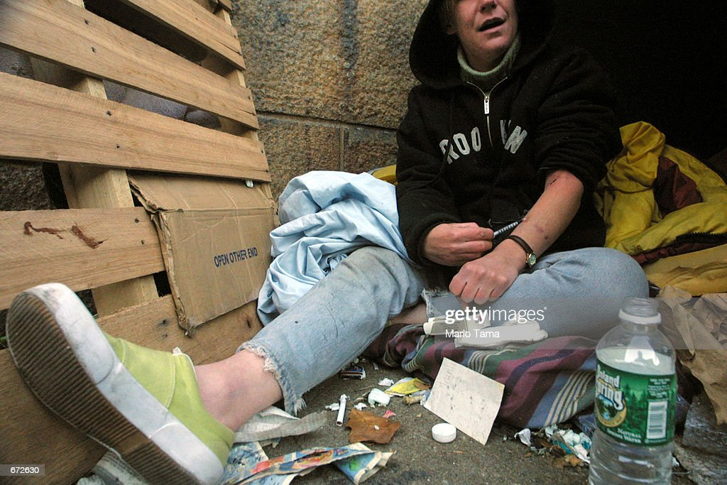 Homeless woman Joan Kimball injects herself with heroin beneath the Manhattan bridge where she lives November 20 2001 in the Brooklyn borough of New...