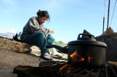 A homeless woman named Sophia sits next to a campfire the she is using to cook rice at a homeless tent city March 23 2009 in Sacramento California...