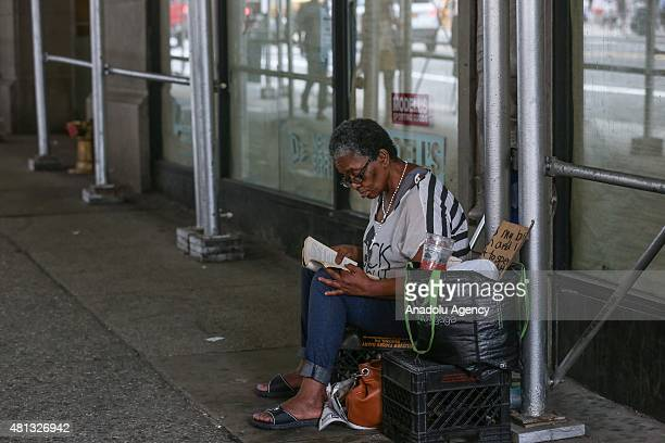 A homeless woman reads her book in New York United States on July 19 2015 The national poverty rate rose to include 132% of the population One out of...