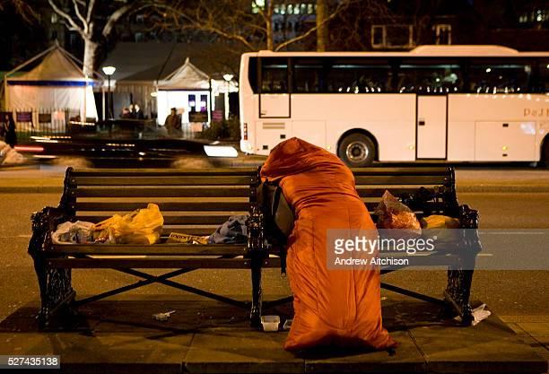 A homeless woman sleeps in her sleeping bag on Victoria Embankment London