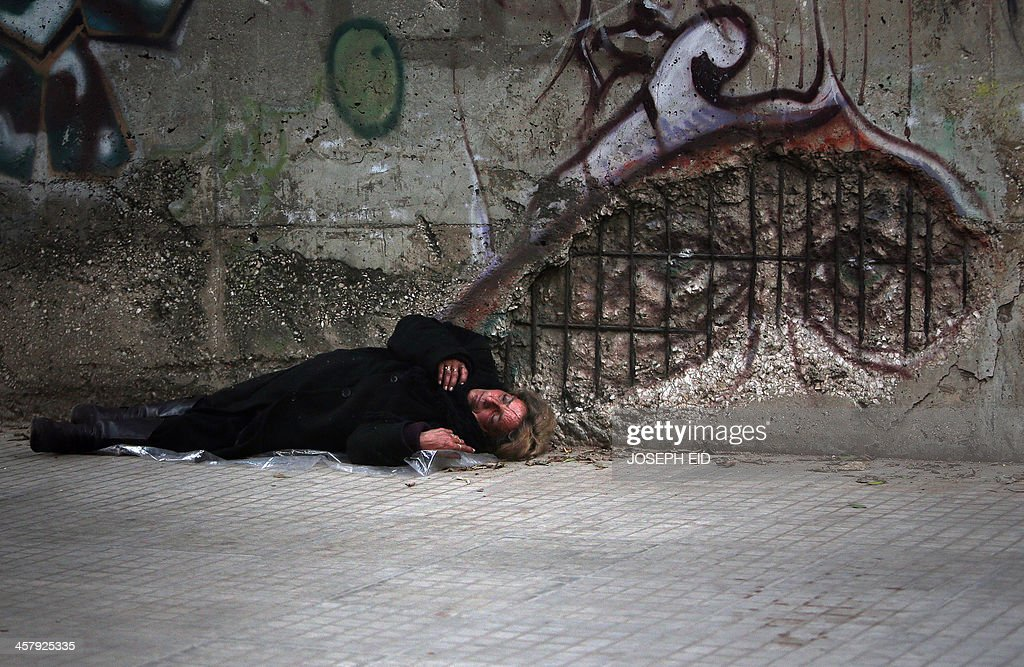 A homeless woman sleeps on the sidewalk of a street in the Lebanese capital Beirut on December 19, 2013.