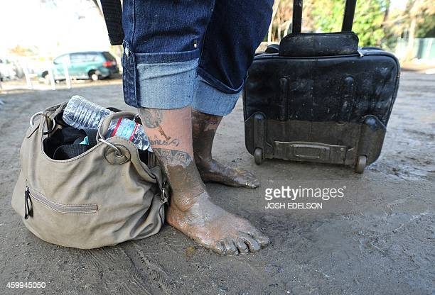 A homeless woman stands barefoot in mud at a Silicon Valley homeless encampment known as The Jungle on December 4 in San Jose California Authorities...