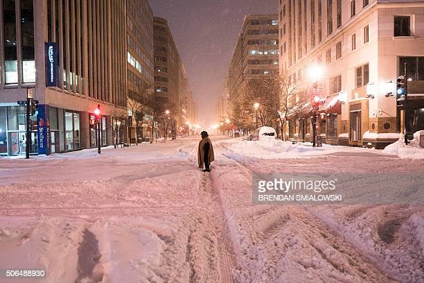 TOPSHOT A homeless woman stands in the street after a snowstorm January 23 2016 in Washington DC A deadly blizzard blanketed the eastern United...