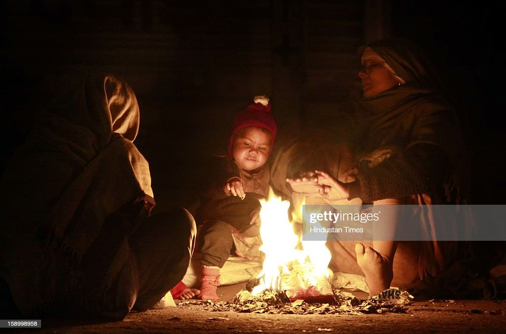 Homeless woman with her children warm themselves around the fire as temperature dips below normal, before sleeping at night shelter at Chandhi Chowk on January 4, 2013 in New Delhi, India. Delhi continued to shiver at a minimum of 2.9 degrees, four notches below normal. Over a 175 people have died so far in the bitter cold in Northern India.