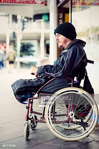 Homeless young invalid man sitting in wheelchair on the street