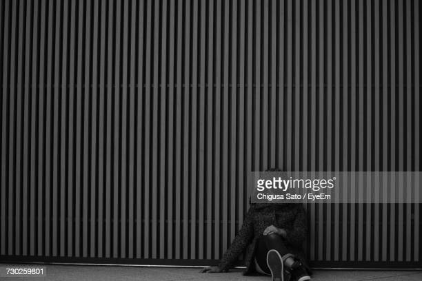 Homeless Young Woman Sitting Against Corrugated Iron