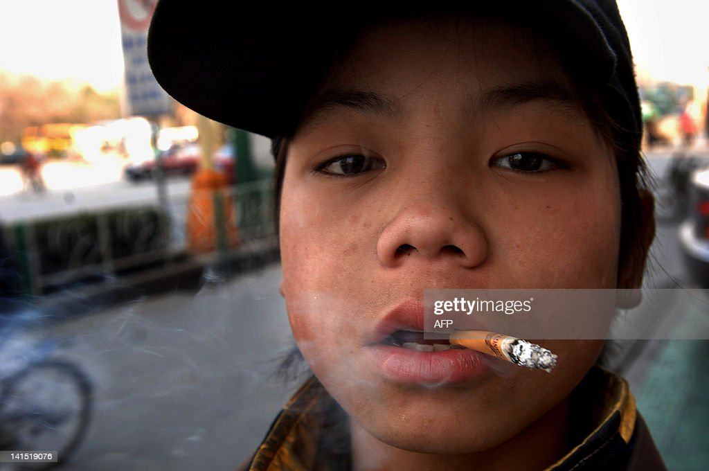 A homeless youngster smokes a cigarette along a street in Hefei, east China's Anhui province on March 18, 2012. China may have made some amazing economic progress in recent years, but the shopping malls and skyscrapers of the major cities are a glittering facade that obscures a darker side to the country's economic transformation, as begging and vagrancy are now rife in all of China's major cities, and the authorities are also being confronted by the growing problem of homeless children. Officially there are now 150,000 children who are forced to live by their wits on the streets of China's cities. CHINA OUT AFP PHOTO