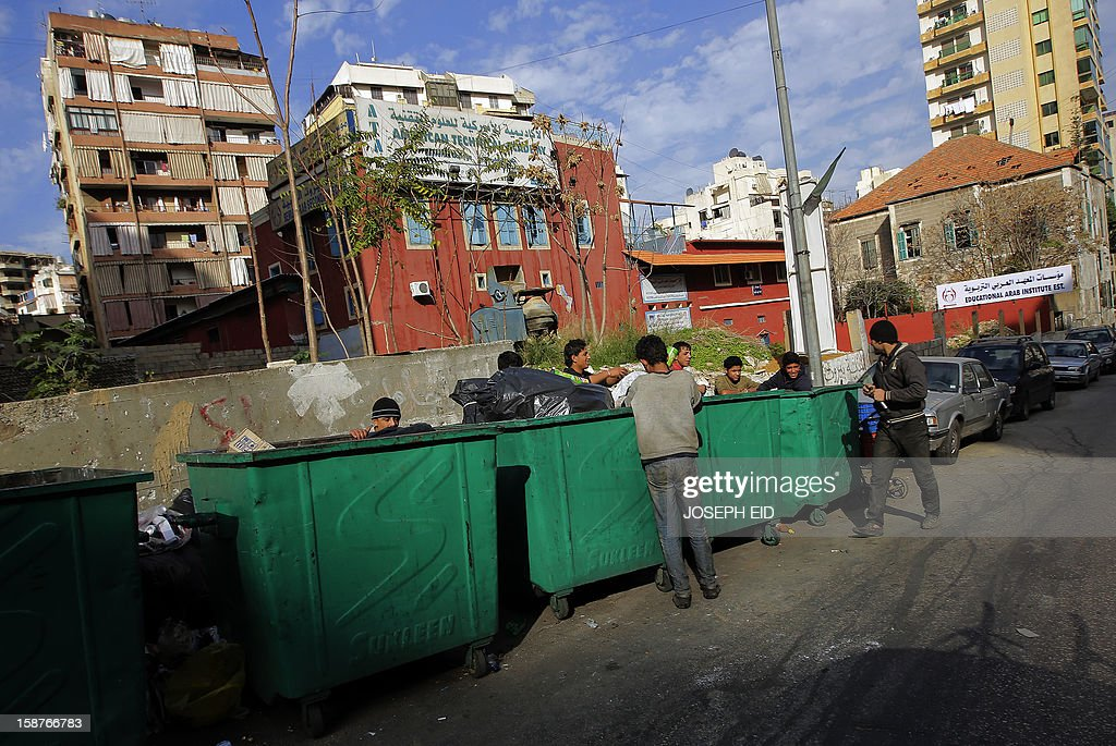 Homeless youth search through the garbage for food canisters, plastic bottles and cans to sell, in Beirut on December 28, 2012.