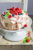 Homemade and rustic Pavlova cake with raspberries and meringue
