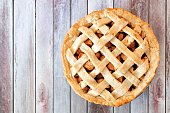 Rustic homemade apple pie with lattice pastry, above view on aged wood