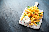 Homemade Baked Potato Fries with Mayonnaise and rosemary on white wooden board.