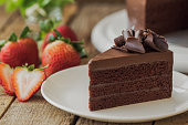 Homemade bakery: chocolate fudge cake decorated with chocolate curl. Triangle slice piece of chocolate cake on rustic wood table for cafe,meeting, coffee break or tea time and birthday party.
